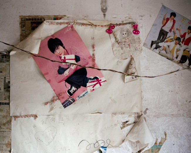 Posters on the wall of an abandoned apartment. Chongqing, China. 2011