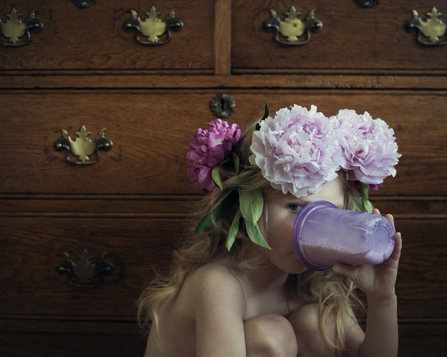 young girl with flowers in her hair drinking milk from a sippy cup