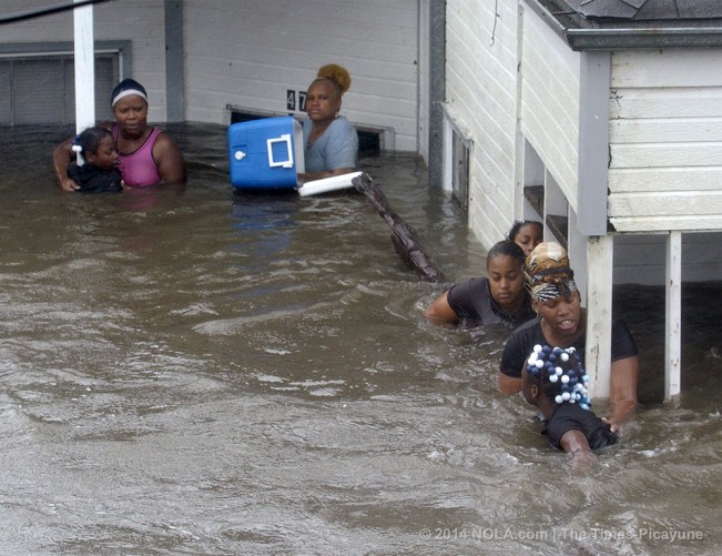 STAFF PHOTO BY TED JACKSON A family of women and children cling to posts on their front porch as rising flood waters force them to evacuate their home on St. Claude Ave in the Lower 9th Ward. They had tried to get into their attic space to no avail. Flood waters raging down St. Claude prevented rescuers from reaching them during the storm. They were planning to swim to safety using the log in the lower right of photo, as spectators pleaded with them to stay where they were until help could arrive. They said they had been clinging to the posts since 8 am. It was now after noon.  Hurricane Katrina. August 29, 2005