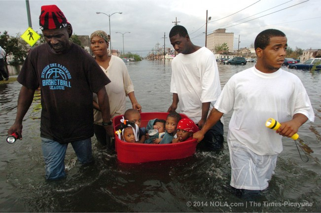 STAFF PHOTO BY JOHN MCCUSKER The hurricane has passed and the flooding has begun Monday afternoon as three men - John Rainey, John Rainey, Jr. and Courtney Davis -  help Terry Fox tug a tub full of children toward an overpass on South Broad Street, August 29, 2005