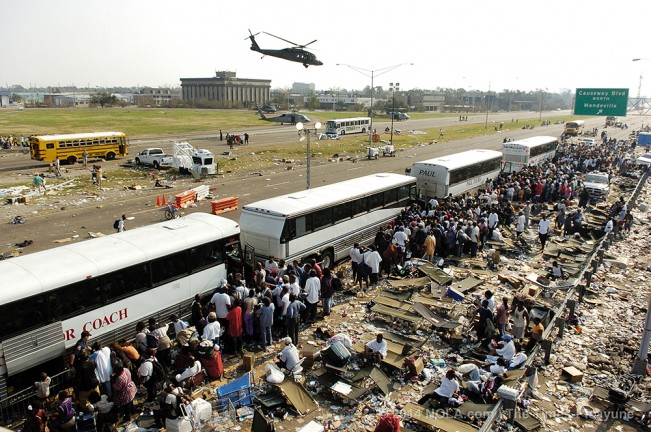 STAFF PHOTO BY ELIOT KAMENITZ As helicopters rush off with the most desperately ill, throngs trapped for nearly a week in New Orleans climb aboard busses at the intersection of I-10 and Causeway Blvd., Saturday, September, 3, 2005, five days after Katrina made landfall.