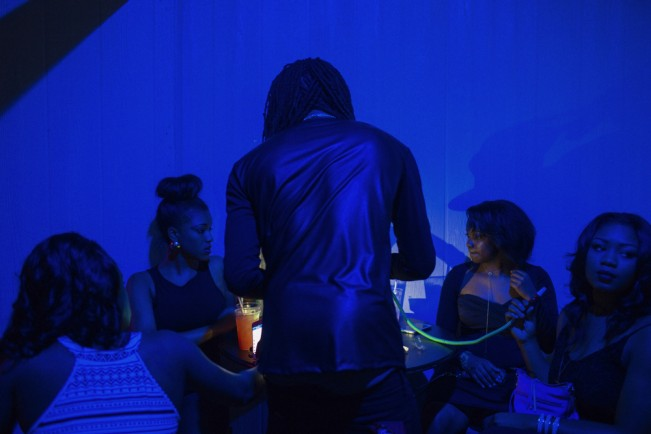 Dexter McCroy (back turned) lights a hookah for young ladies at a party at Main Attractions in Greenwood, Mississippi on November 22, 2014.