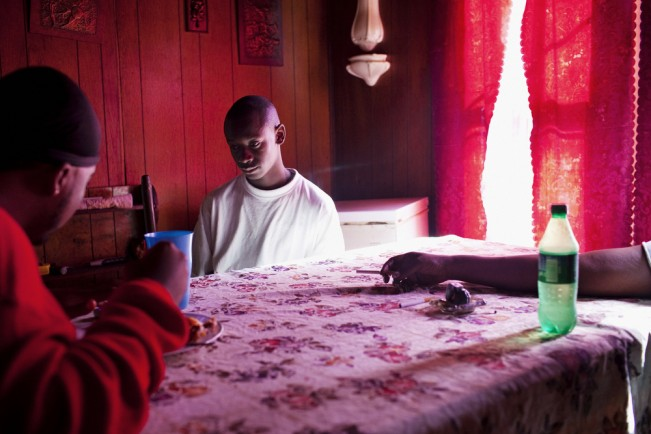 "(L-R) Jabari Wilson sits next to his cousin Korwin ""Quan"" and mother Ellen in the dining room of the home he shares with his mother, sister Nikki and her girlfriend Dominique in the Baptist Town neighborhood of Greenwood, Mississippi on Saturday, November 6, 2010. Jabari and his sister Nikki both work to support their mother who has a number of health problems and is unable to work. Quan (center) lost his mother in a car accident as a child and has been raised by his grandmother ever since."