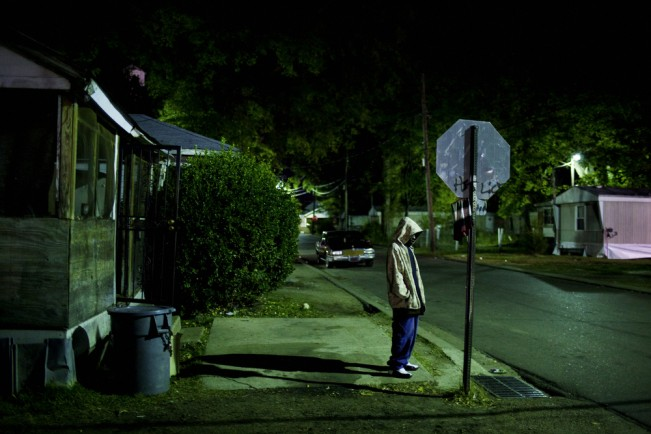 A young man lit only by the dim glow of street lights stands on the corner of Young and Pelican late at night in the Baptist Town neighborhood of Greenwood, Mississippi on Thursday, November 4, 2010.
