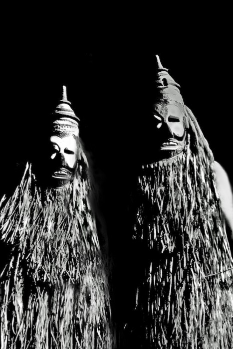 Two Mardi Gras maskers in New Orleans resemble ancient tribal members in this black and white photo portrait.