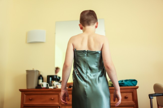 Preparing for the fashion show in a prom dress donated by friends of the camp.