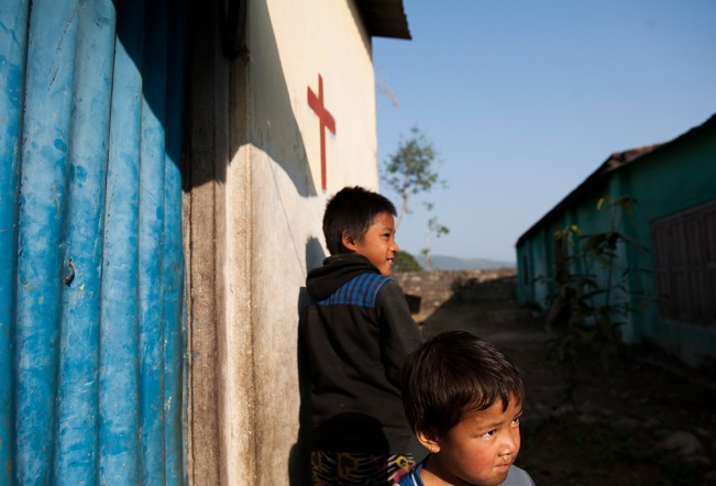 Rubin, left, and his Jyoti stand in front of their home on Tuesday, February 3, 2015 in Hetauda, Nepal. Their father recently converted to Christianity, so he marked their home with a cross. Approximately one percent of Nepalese people are Christians.