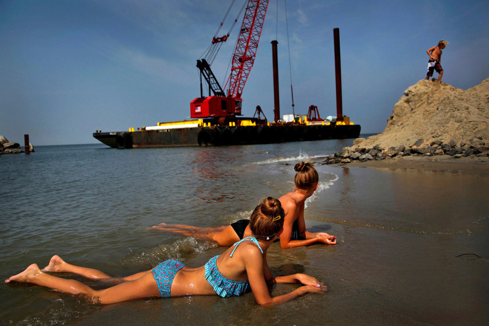 Twins, 2013 People enjoy the beach next to some heavy equipment in place for jetty construction on Willoughby Spit in Ocean View in Norfolk, Va., on Tuesday, August 27, 2013.