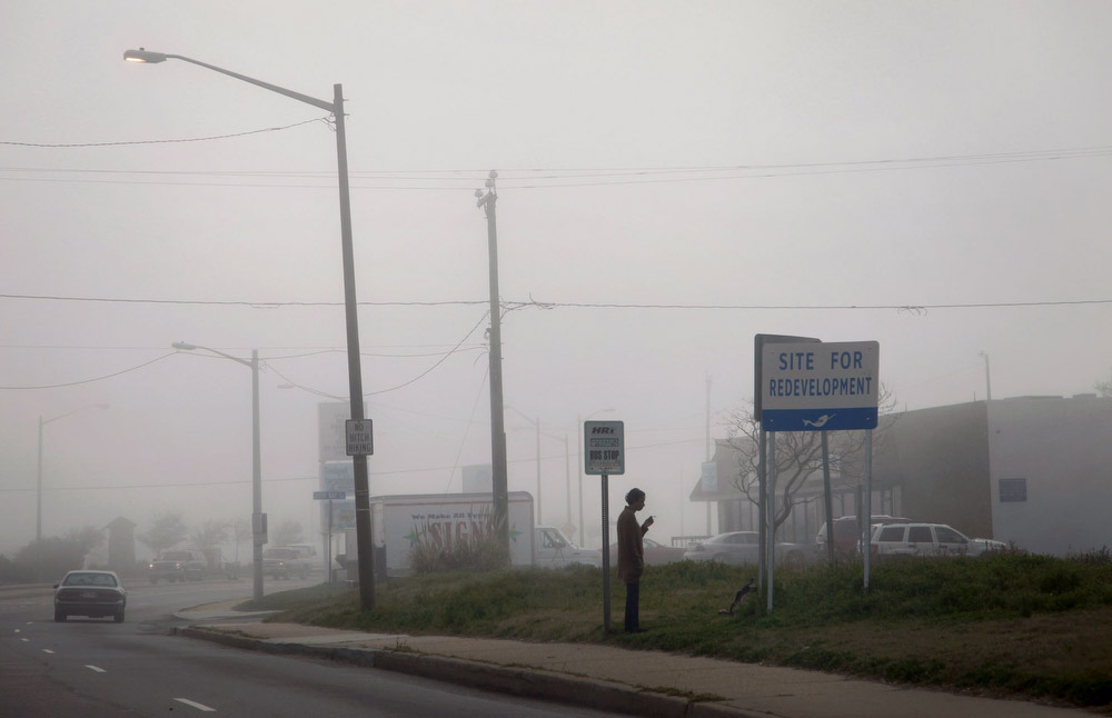 Redevelopment, 2012 On a foggy morning, a woman waits at the bus stop near the site of a demolished motel. The beach and former amusement park in Ocean View were popular tourist destinations from the late-1800s until the 1970s. Recent redevelopment is aimed at replacing motels and cottages with upscale properties.