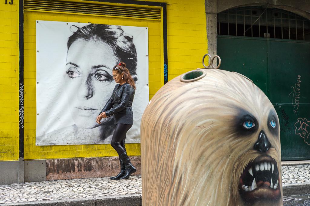 Lissabon_ Eine Frau passiert eine Theaterreklame und einen Glassammelbehälter  im Rotlichtviertel nahe den Cais do Sodre.