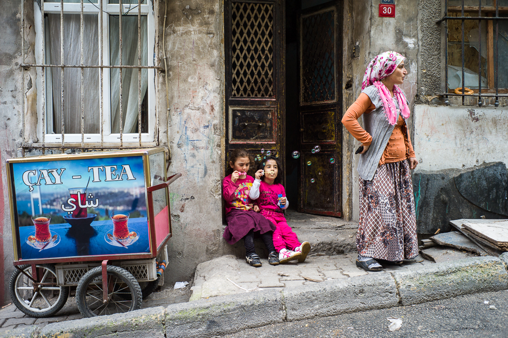 Zwei Mädchen sitzen in Tarlabashe vor der Haustür und spielen mit Seifenblasen; Istanbul, Türkei