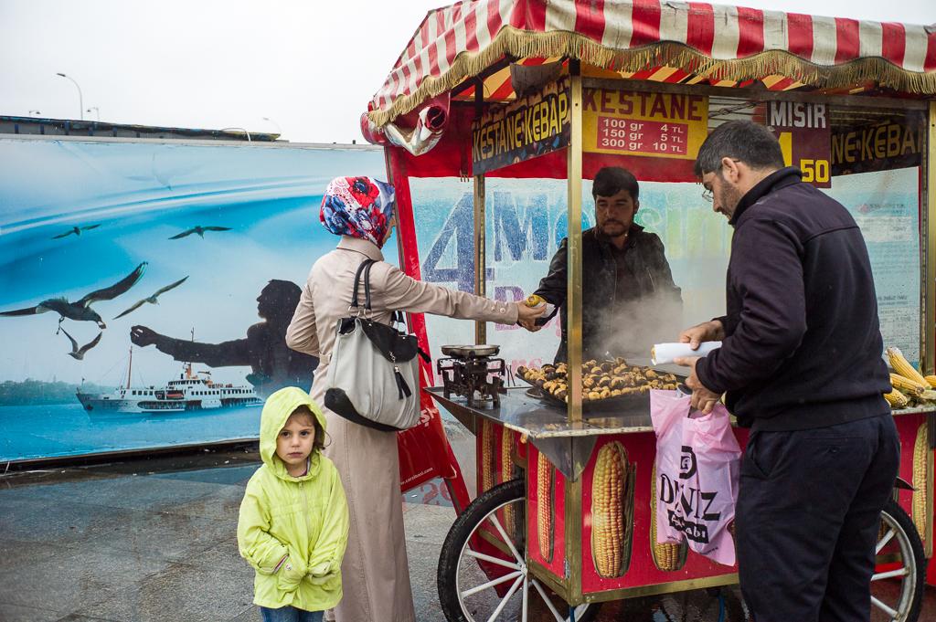 Eine Familie kauft geröstete Maiskolben am Hafen in Eminönü; Istanbul, Türkei