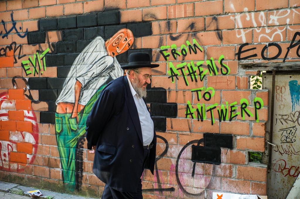 Ein jüdischer Diamantenhändler passiert eine Graffiti-Wand in Antwerpen, Belgien