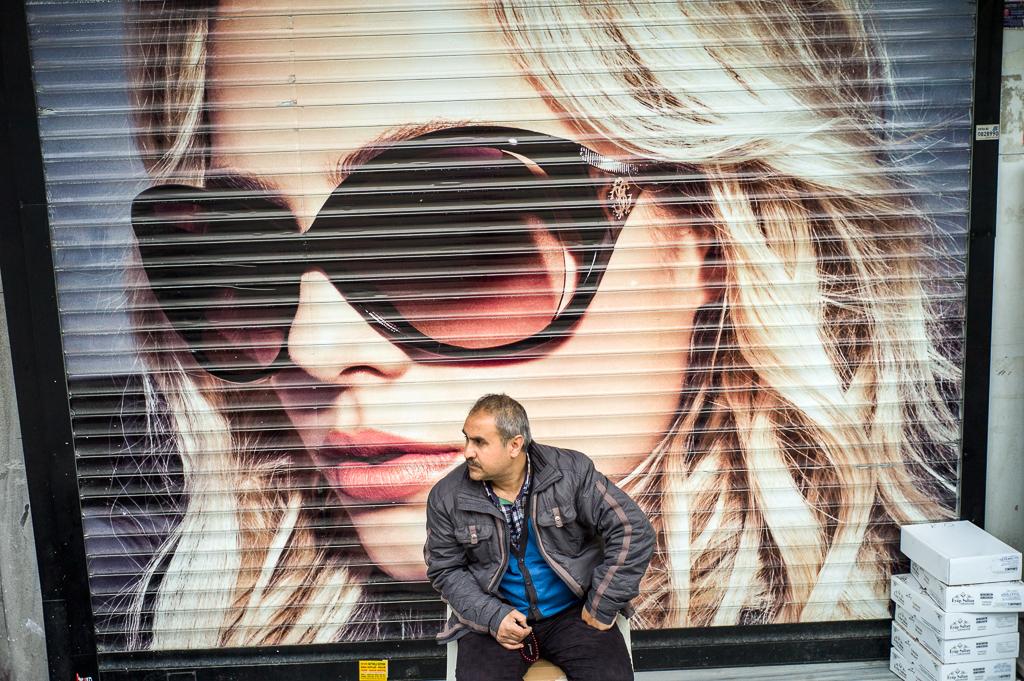 Ein Mann sitzt in Aksaray vor einem mit Werbung beklebten Rolladen eines Geschäfts; Istanbul, Türkei