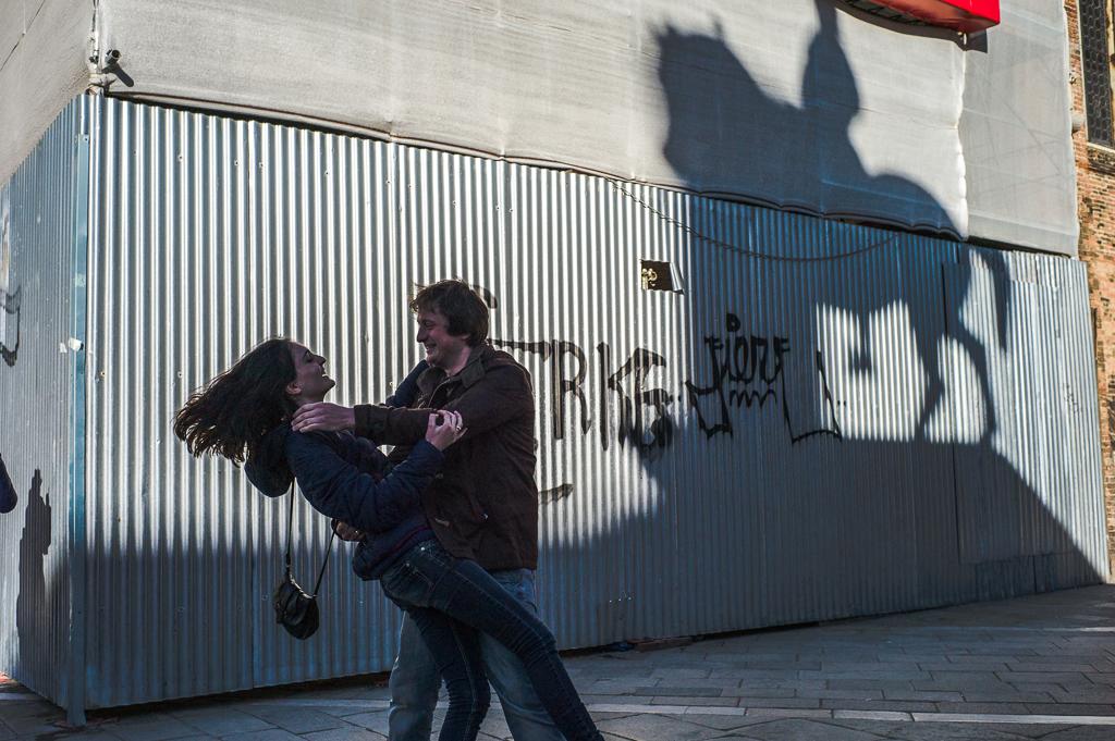 Ein junges Paar tanzt in Venedig zur Musik eines Akkordeonspielers unter dem Reiter- Denkmal von Colleoni