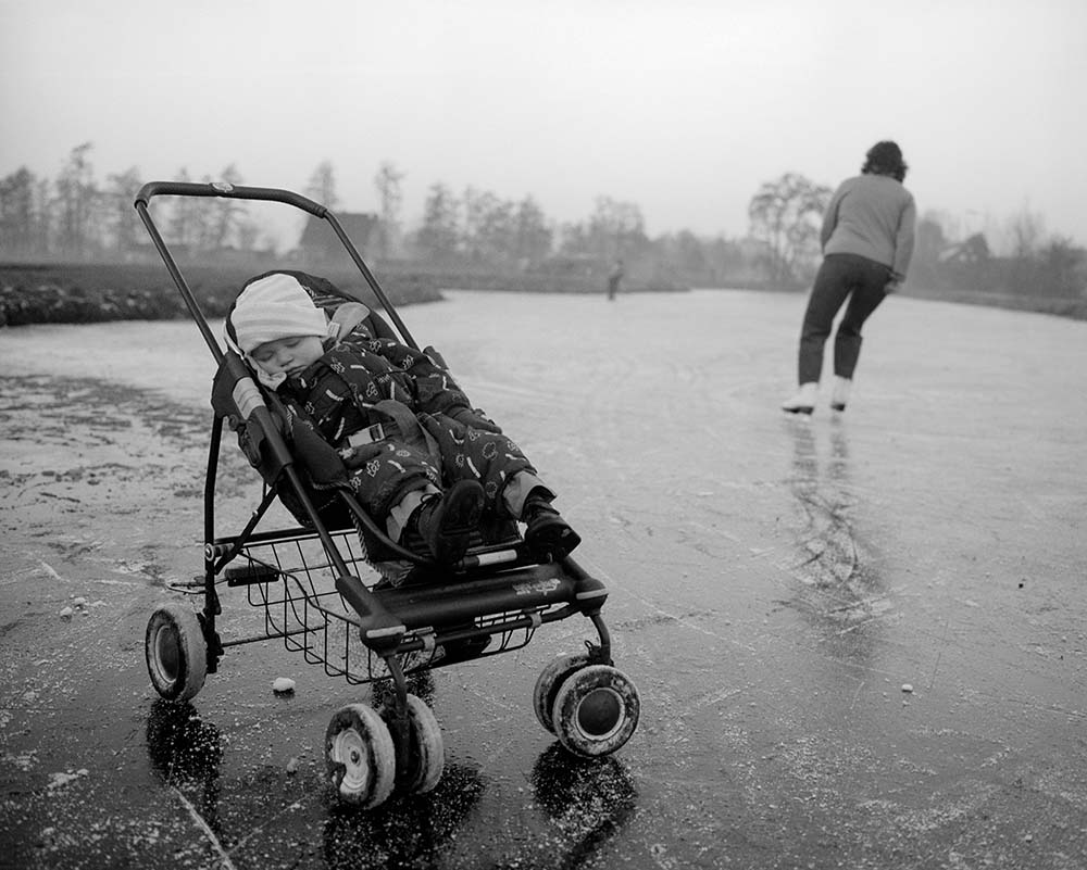 Farmer Monique van der Laan is ice skating on the frozen canal in front of the farm, while her son Timo sleeps, De Beekhoeve, December 2007, from the book The Other Farm.