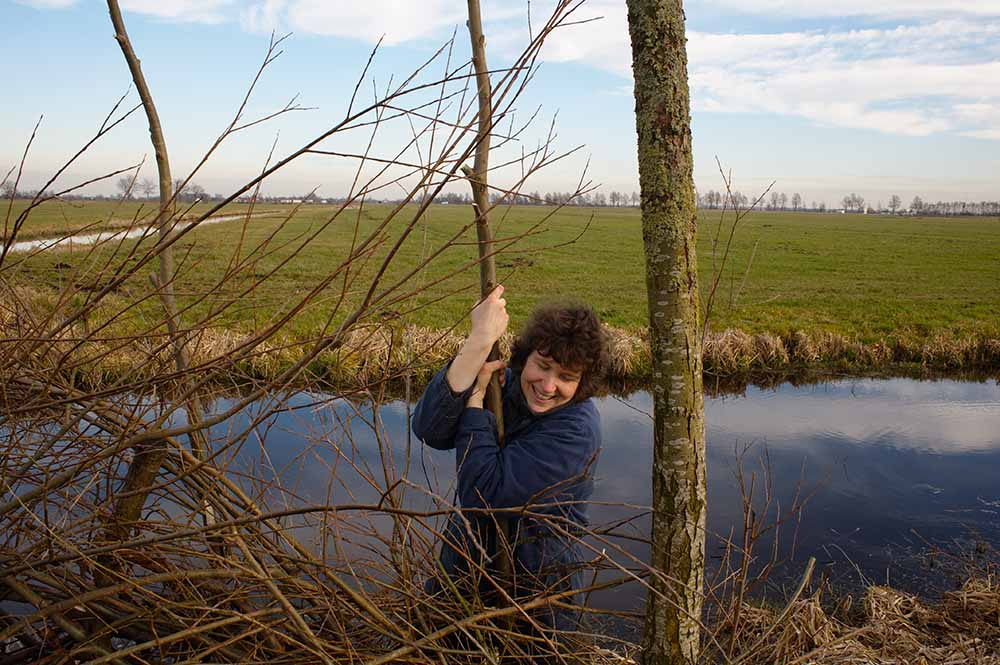 Monique is planting a pollard willow branch as part of a bird screen. People who walk the public trail through the pastures will be able to observe meadow birds from behind it without disturbing them. De Beekhoeve, February 2009, from the book The Other Farm