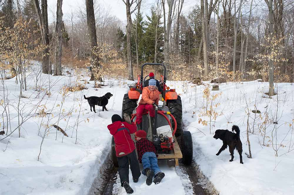 At locations that are not suited for drainage by tubes, the maple sap is still collected in steel buckets hanging under taps from the tree trunks. The sap is gathered in a tank that sits on a flat trailer wagon behind a tractor. Ross Thurber gets help emptying the buckets from his children Isabella and Henry, and his nephew Calvin (left). Dogs Trooper and Clover run along. Lilac Ridge Farm, March 2011, from the book The Other Farm