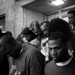Rev. Michael Pfleger of St. Sabina Church embraces young men who are working to break the cycle of violence during a prayer service. Auburn Gresham, Chicago, 2013