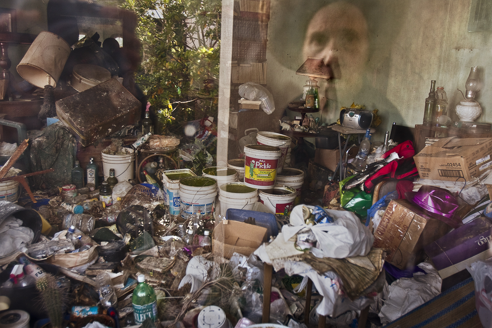 Lee is reflected in a window of her house. Soon after this image was made, her son cleaned out the house, filling six dumpsters in the process.