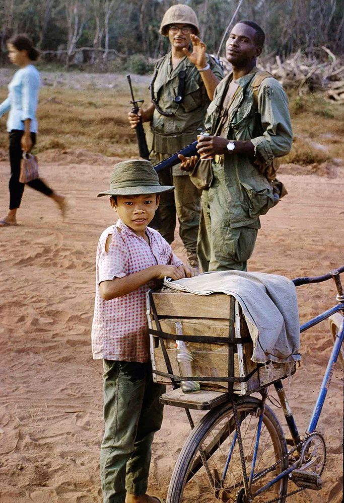 "Image 20 Bill NoyesCOKE KID AND OUR PLATOON LEADER, LT TIMOR, WITH HIS RTO (RADIO, TELEPHONE OPERATOR) WHO WAS KNOWN AS ""WATER BUFFALO""""HARD SPOT"" ALONG ROUTE 239 AS IT ENTERED THE BEN CUI RUBBER PLANTATION ACROSS THE SAIGON RIVER FROM DAU TIENG, VIETNAM FEBRUARY 1969Bill NoyesSergeant E-5, 3rd Platoon, B Company, 2nd Battalion of the 22nd Regiment, 25th Infantry Division - Army Vietnam September 1968 - September 1969"