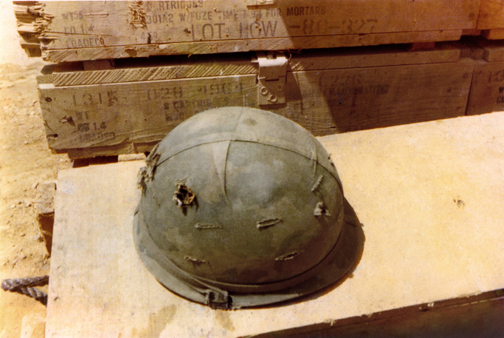 Image 38 Merle ElliottMY HELMET WITH TWO BULLET HOLESFIREBASE LZ STINSON, QUANG NGAI PROVINCE, VIETNAMMerle ElliottSpecialist 4 E-4, 198th Light Infantry Brigade, 1st Battalion/52nd Infantry, Company C 1/6, Americal Division – Earned the Combat Infantry Badge, Purple Heart and Army Commendation MedalVietnam 7/15/1970 – 7/14/1971
