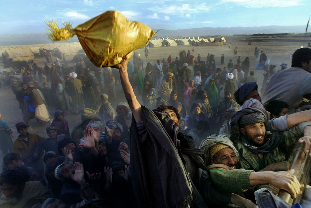 Chaman, Pakistan, December 4, 2001. Afghans at the Killi Faizo refugee camp desperately reach for bags of rice being handed out to the thousands who escaped the bombardment in southern Afghanistan during Operation Enduring Freedom.