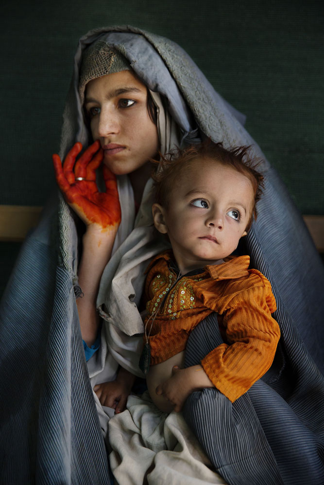 Razima holds her two-year-old son, Malik, while waiting for medical attention at the Boost Hospital emergency room. (Lashkar Gah, Helmand Province, June 23, 2014)