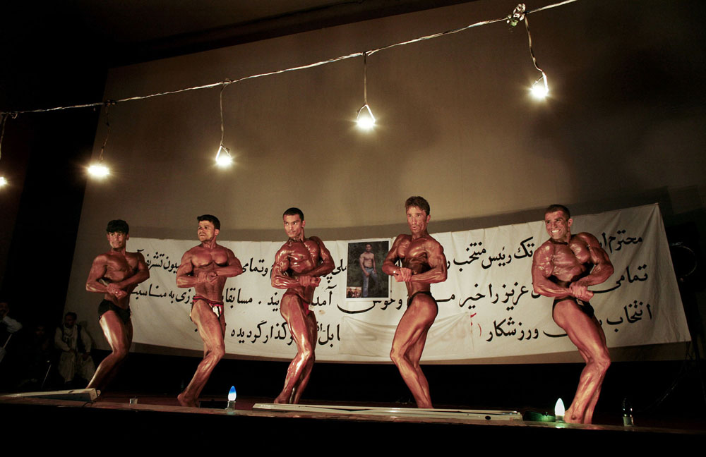 KABUL, AFGHANISTAN - AUGUST 6: Afghan bodybuilders compete in the 55-60kg category during a regional Bodybuilding competition August 6, 2007 in Kabul, Afghanistan. Bodybuilding is a very popular sport in Afghanistan in a country where men like the image of being physically strong. It's affordable for most Afghans and its popularity is growing in many provinces. Photos of Arnold Schwarzenegger are still hanging in many local gyms as their iconic image of a muscle bound male.  (Photo by Paula Bronstein/Getty Images)
