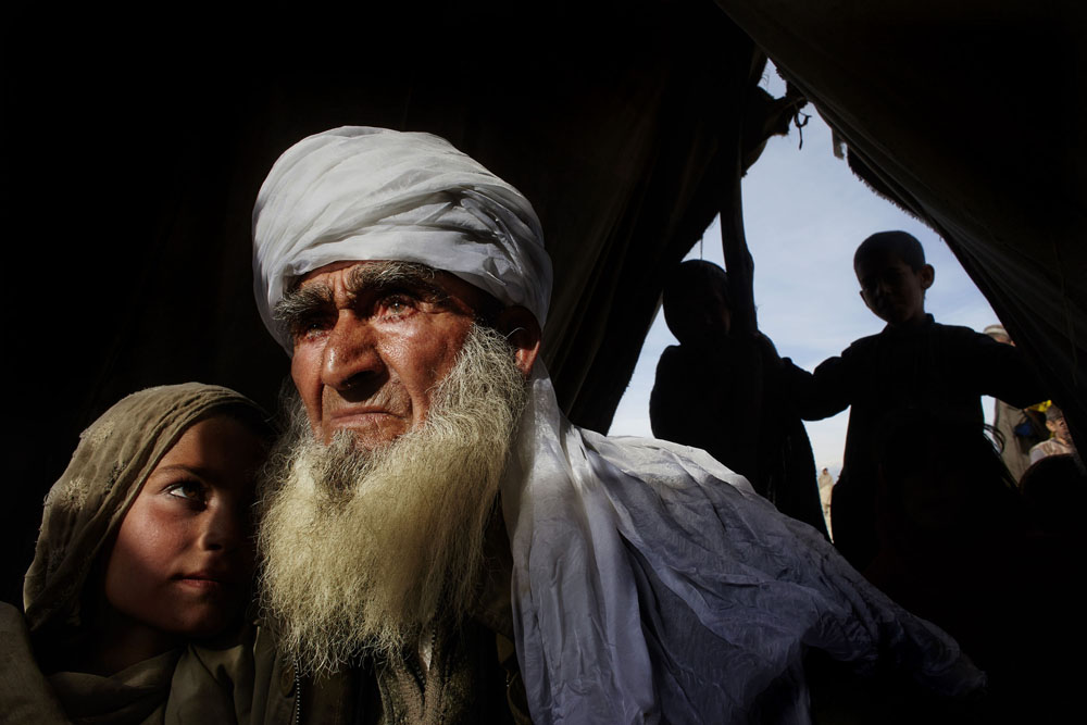 Surobi, Nangarhar Province, February 7, 2009. An elderly man holds his granddaughter in their tent at a refugee camp after they were forced to flee their village, which US and NATO forces had bombed because, they claimed, it was a Taliban hideout.