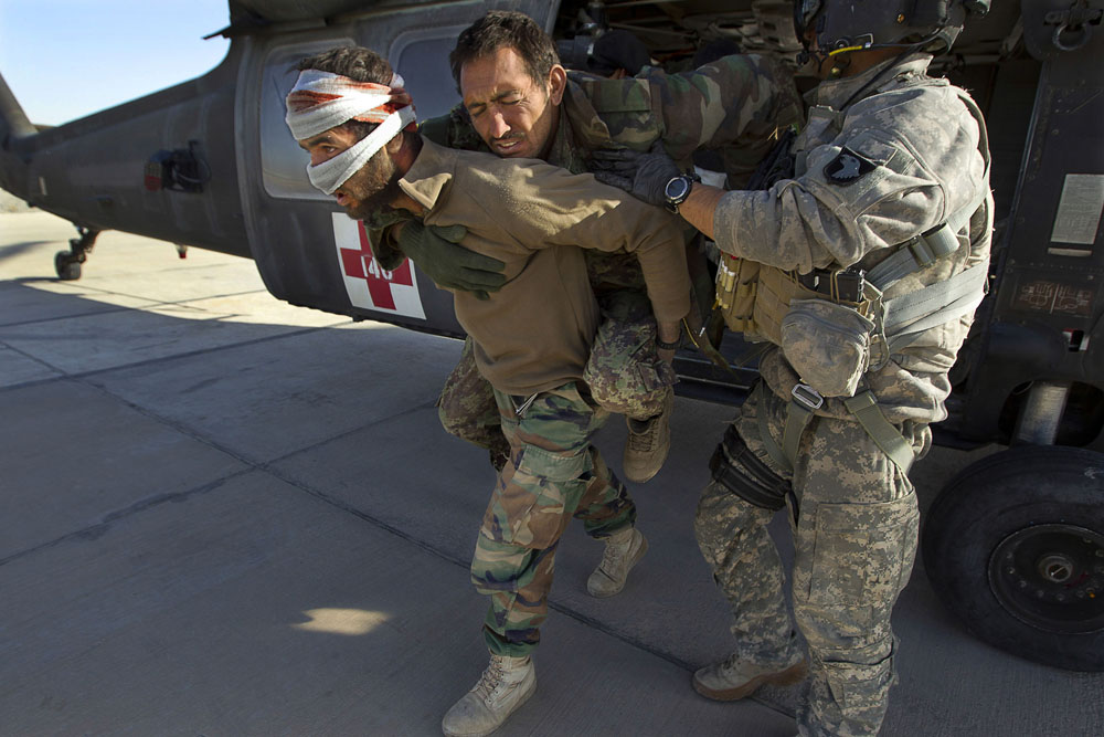 U.S Military Sargent Jay Kenney, 26, (R) with Task Force Destiny, assists wounded Afghan National Army soldiers off a Blackhawk helicopter after they were rescued in an air mission in Kandahar.  December 12, 2010