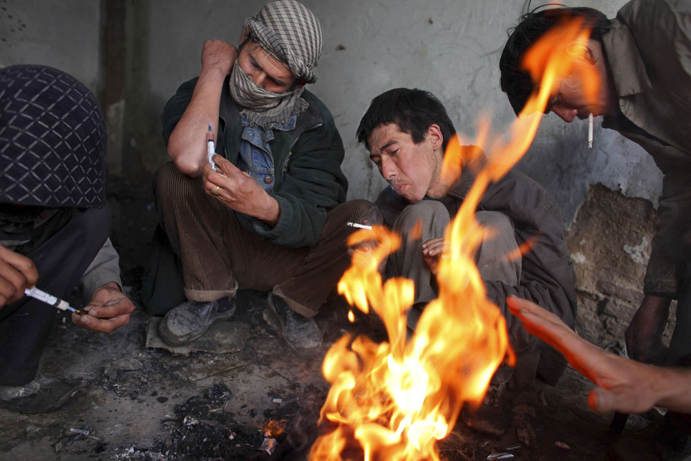Kabul, February 9, 2009. Addicts inject heroin while trying to keep warm inside the abandoned Russian Cultural Center, which the capital city's addicts use as a common gathering point. Heroin is readily available, costing about one dollar a hit.
