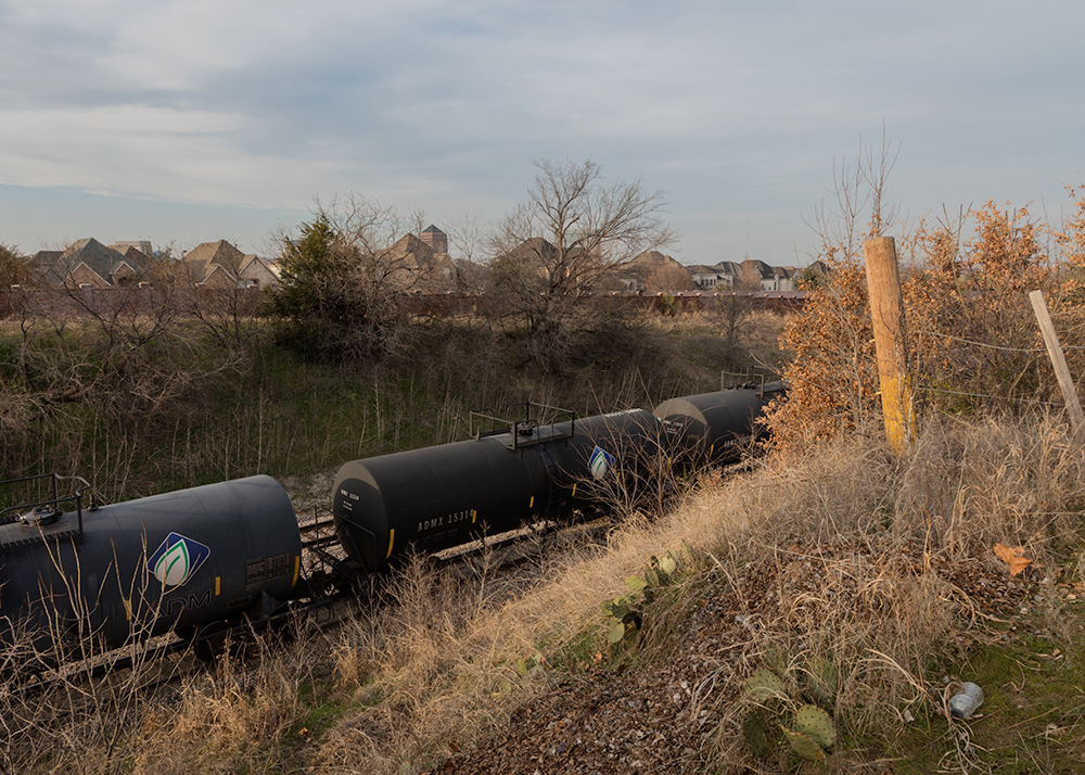 Tank Cars Parked On Top of a 12-inch High Pressure Explorer Pipeline Outside of ExxonMobil Pipeline Company's Storage Facility. University Park Neighborhood and Highlands School; Irving, Texas. Five earthquakes epicenters have occurred within 2000 ft. of this area.