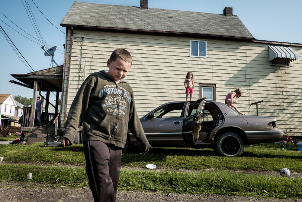 Children play on their dad's demolition derby car outside of their home in West Aliquippa, Pa. USA, on May 8, 2015. Since 1987, the city has been designated as a distressed municipality under the state's Act 47, a law that created a recovery program that's helped some 29 municipalities in the state stay afloat. The city now has fewer residents now than the local steel mill had employees (14,000) in its heyday. The mill closed down for good 20 years ago. With few good job opportunities available, children who grow up in the area may be faced with tough economic times when they are ready to join the workforce.