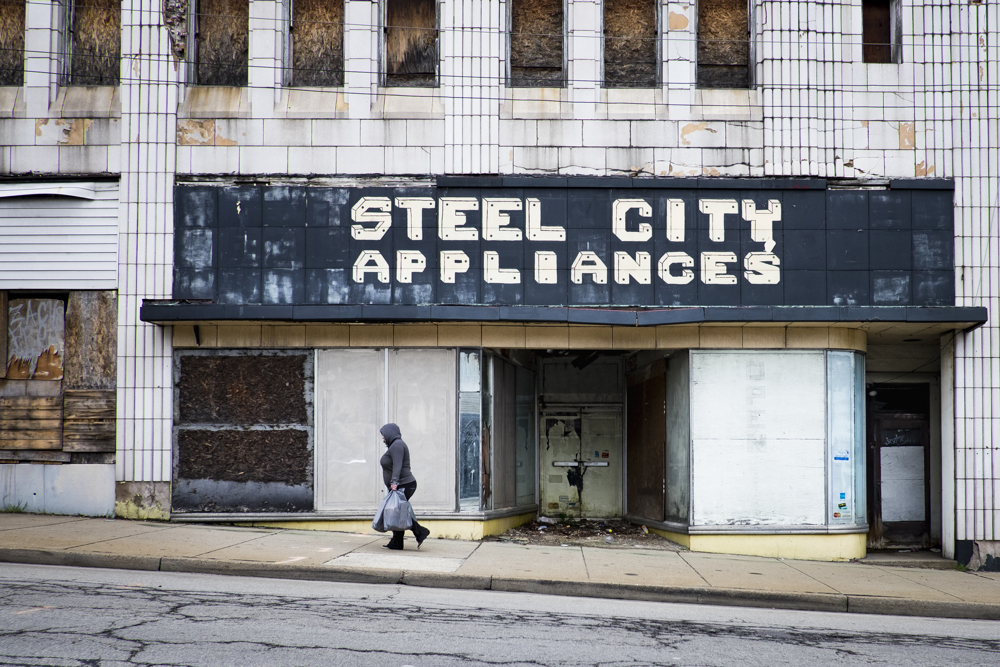A woman walks up one of the main streets in Clairton, Pa., past the old Steel City Appliances store. About three-quarters of its main street is boarded up including the laundry, the grocery store, three out of five banks, the three cinemas, and most cafes and shops. When the Clairton Coke Works employed 5,000 workers and ran three shifts, Clairton had three movie theaters and four car dealerships. Now the plant employs 1,300 workers and residents must drive five miles out of town to buy food since there is no longer a grocery store in town.