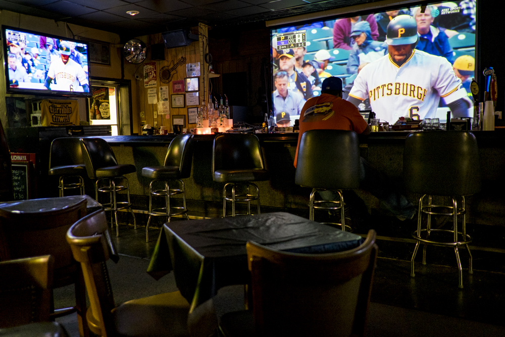 A lone patron watches the Pittsburgh Pirates play baseball on the big screen at the Valley Hotel Bar and Grill outside of Clairton Pa. Built in 1863 and was originally called The Granger Hotel, it was positioned in between two of the largest steel mills in the area. The Valley Hotel has long been the local watering hole for mill workers after a long day, or night, of work. With the local mills running at just a fraction of full capacity, the bar has struggled in recent years.