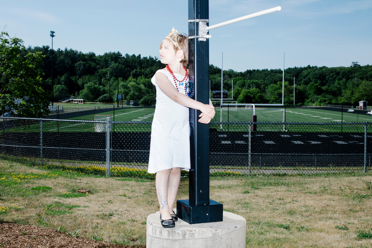 "Cerys Coffey, 5, of North Hampton, MA, stands on a lamp post while waiting to enter a rally for Democratic presidential candidates Hillary Clinton and Bernie Sanders at Portsmouth High School in Portsmouth, New Hampshire, on Tues., July 12, 2016. Cerys wore a dress reading ""A woman's place is in the White House"" and other Hillary Clinton campaign items. She was there with her family. At the rally, Sanders officially endorsed Clinton as the Democratic nominee for president."