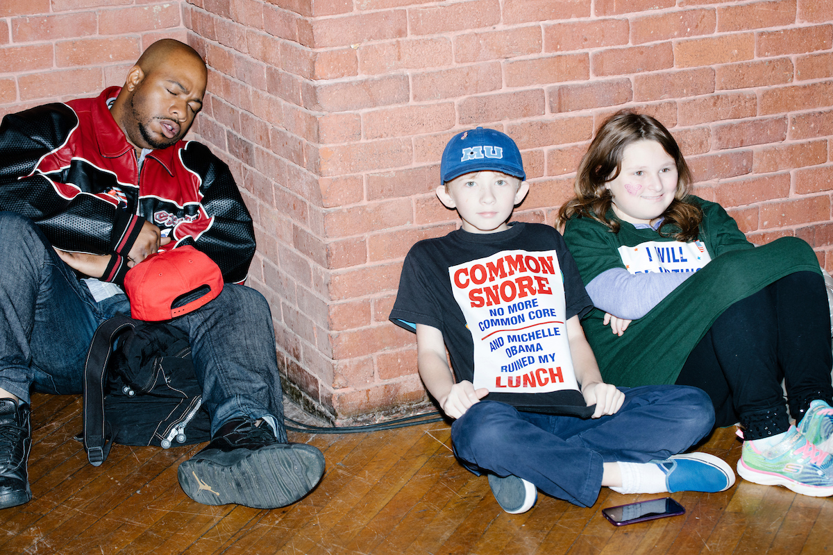 "Montgomery Crane, 14, (from right), brother Frankie Crane, 11, of Arlington, Vermont, and Elijah Drake, 32, of Brooklyn, New York, sit on the ground before a campaign rally for Republican presidential nominee Donald Trump at the Radisson Hotel in Manchester, New Hampshire, on Fri., Oct. 28, 2016. The Cranes traveled to the rally with their parents. Drake has been to four other Trump events and considers himself a strong supporter of the candidate. To attend this rally, Drake got on a Greyhound bus in New York at about midnight and traveled for 7 hours. He would be getting on a bus back home immediately after the rally. Drake said of Trump, ""He's the first and last person I'll ever vote for. If it's not somebody of his caliber, I'm not voting again."""