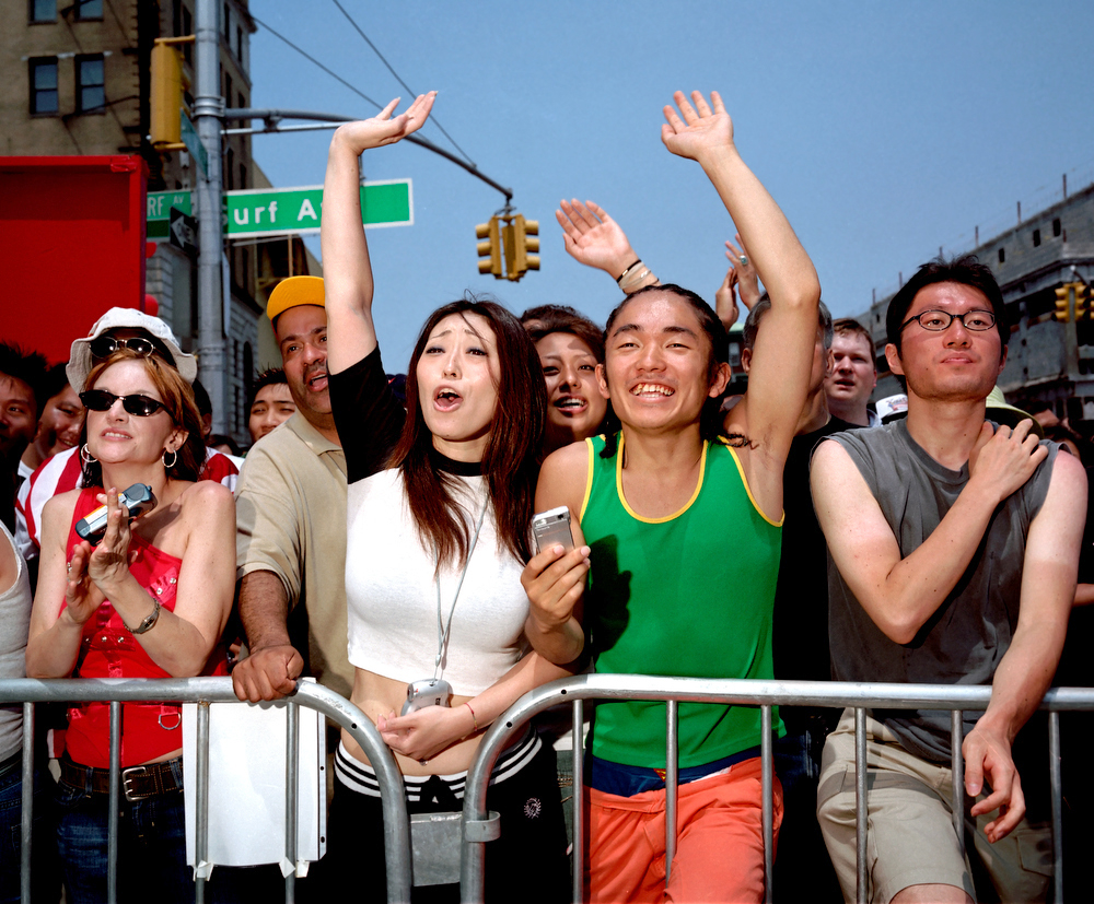 Coney Island, New York, 2005 Fans of Japanese Hot Dog Eating Contest winner Takeru Kobayashi, wave to garner his attention from the sidelines of the contest.  Nathan's Hot Dogs hosts the Hot Dog eating contest annually on the fourth of July.