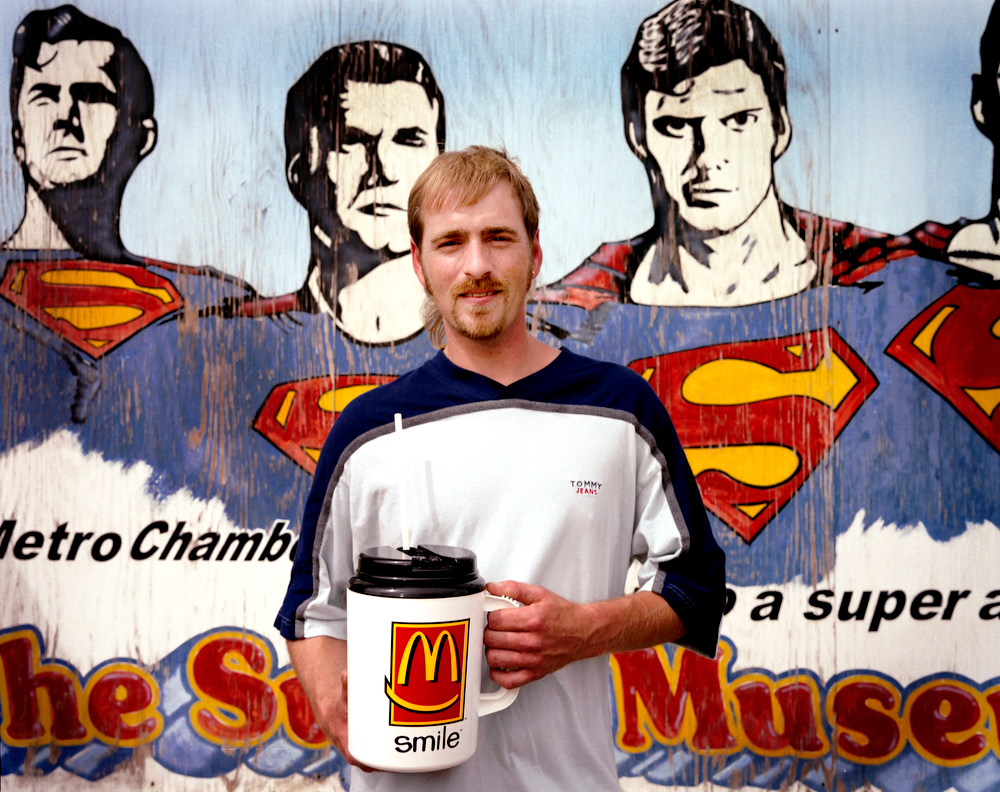 Metropolis, Illinois, 2005 A man poses in front of a billboard advertising the Superman museum with a large plastic drink mug, bearing the McDonald's logo.