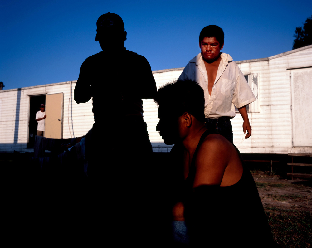 Immokalee, Florida, 2006 Migrant day laborers from Mexico and Guatemala outside their trailer at day's end.  Life for migrant laborers is a mostly ascetic existence, living without the comforts and familiarities of home, with a group of strange men, bound by a common language but little else.  These migrants pick tomatoes, many of which end up as products in fast food restaurants.