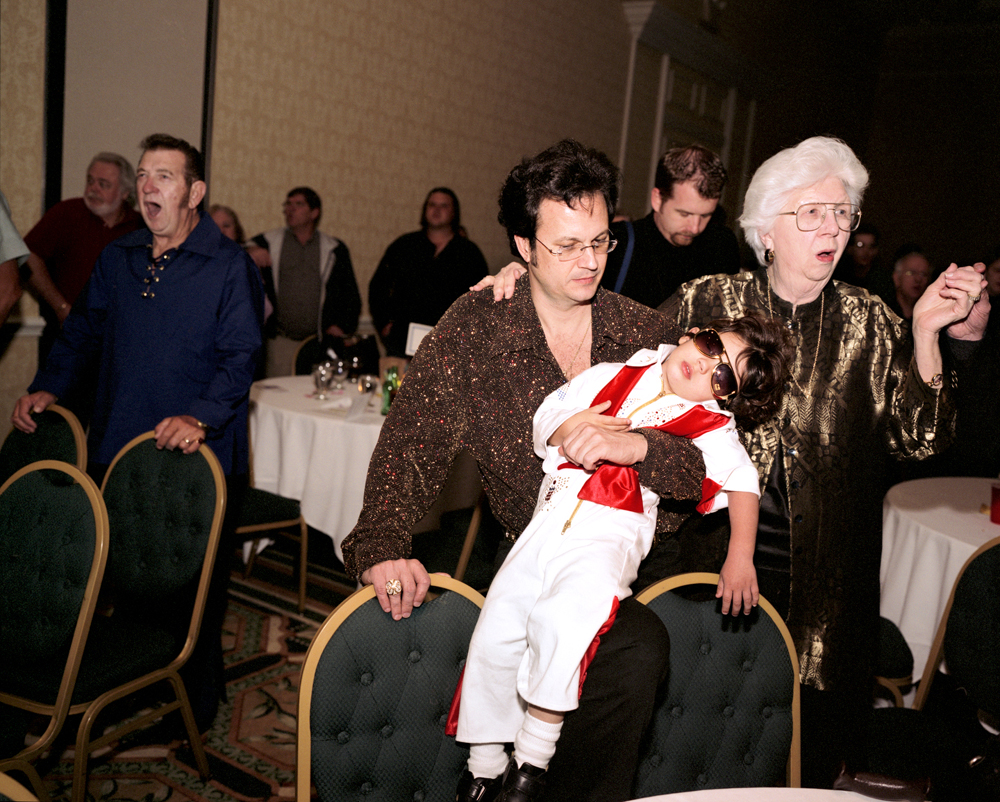 Sleeping Elvis, Kissimmee, Florida, 2005 A boy sleeps in his fathers arms at the culmination of the EP Continentals, the oldest Elvis' Fan Club, annual fundraiser in Kissimee, Florida.  At right is Elvis' last nurse, Marian Cocke.