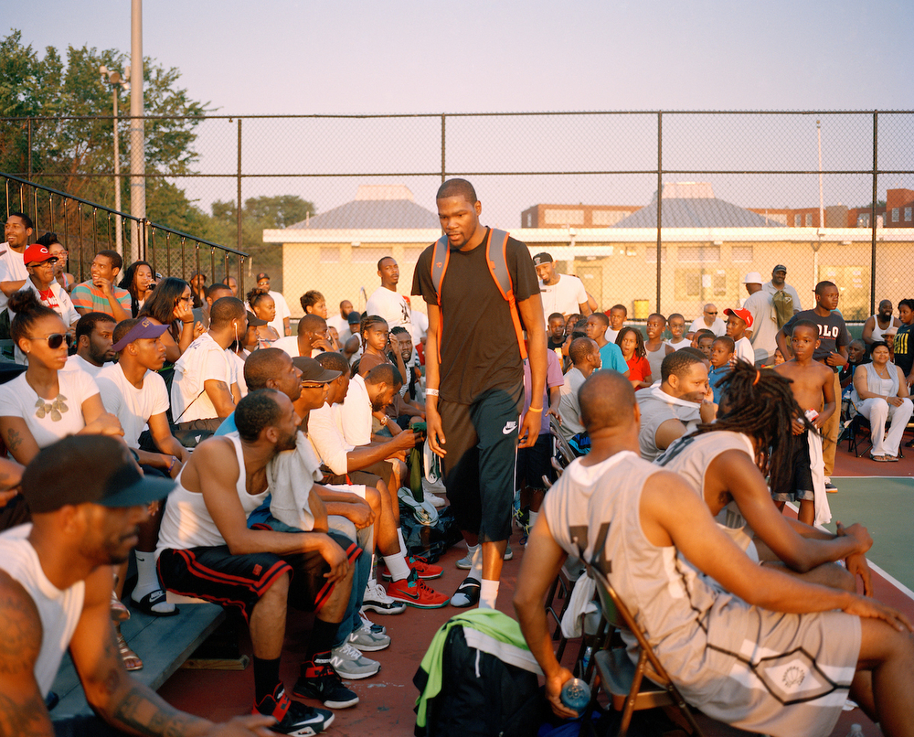 Oklahoma City Thunder and Washington DC native, Kevin Durant makes his way to the bench to pick up his uniform for a summer 2013 George Goodman Basketball League game at Barry Farms Dwellings basketball courts in Southeast Washington, DC. Durant, who has been an NBA All Star and scoring champion has played in the Goodman League since he was a teenager. He often makes appearances throughout the summer.