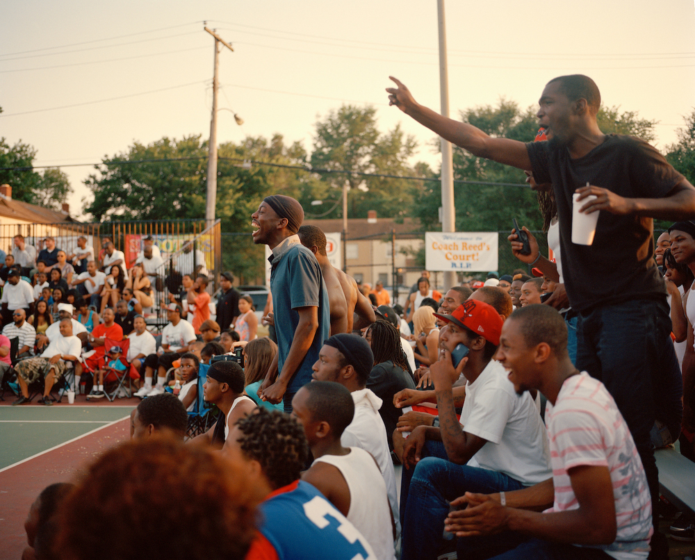 Members of the BF Crazies section cheer after a dunk during a summer 2013 George Goodman Basketball League game at Barry Farms Dwellings basketball courts in Southeast Washington, DC. A few seating sections have been given nicknames such as Season Ticket Holders, 9-5 Crew, and The Lane Mob.