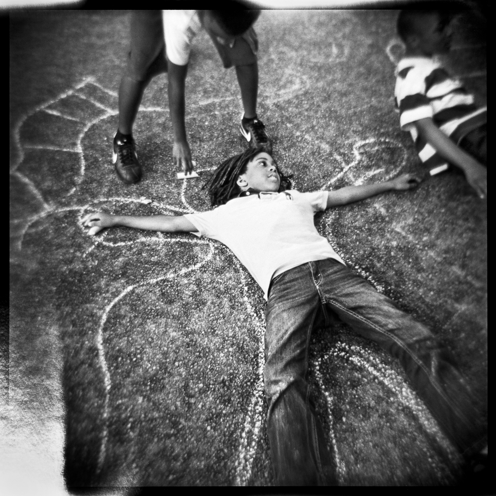 Children draw chalk outlines on the street as part of the festival art activities for children.  Young boy whose shadow is being drawn is Grady Champion Jr.