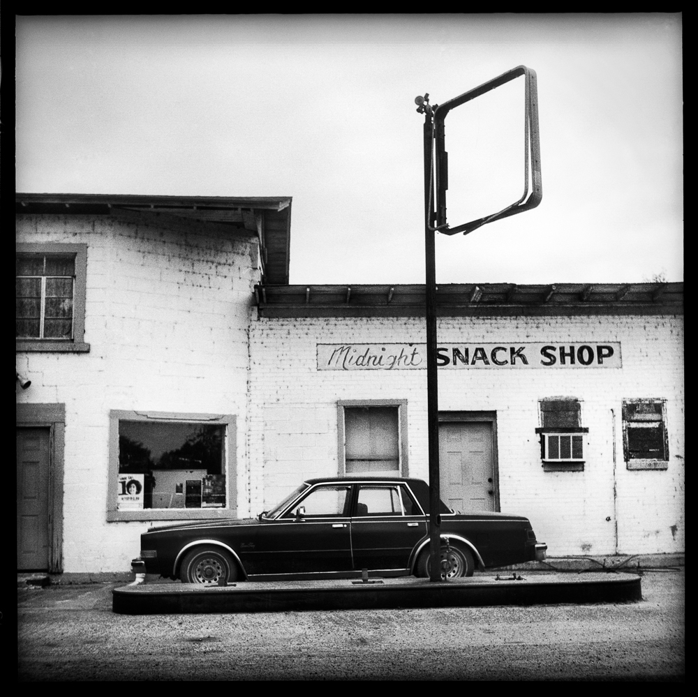 Old vintage car sits in front of an abandoned gas station and snack shop.