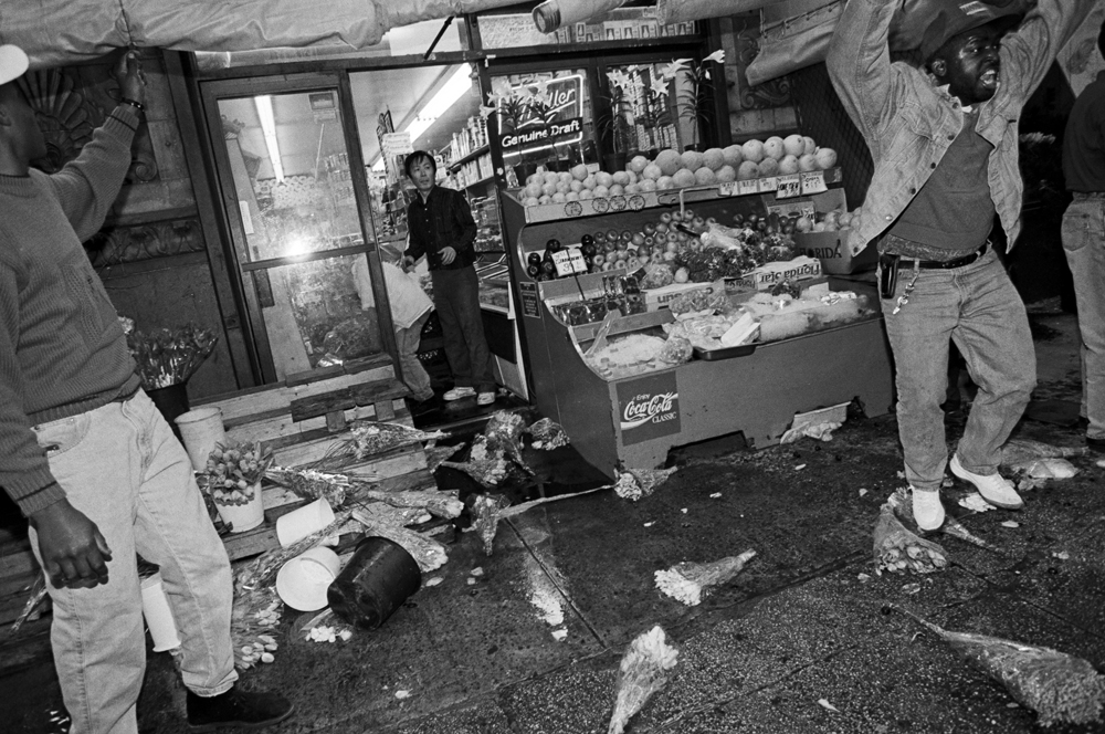 NYC protesters take to the streets in response to the acquittal of the officers involved in the beating of Rodney King. Some Asian-owned groceries such as this one were vandalized.  April 1992.   © Linda Rosier