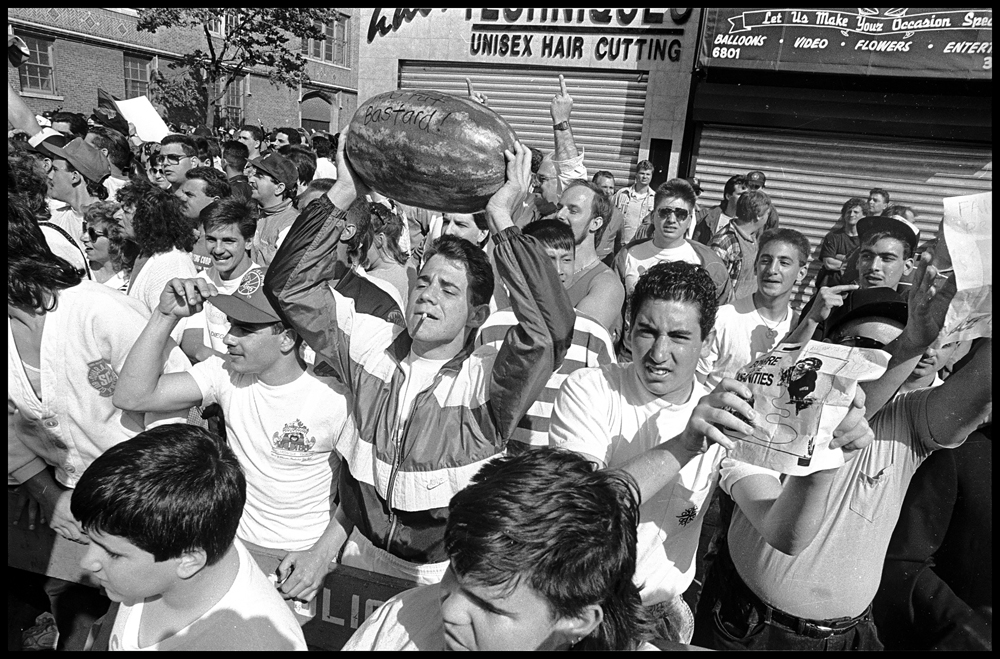Bensonhurst residents hold up watermelons to mock African American protestors who took to the streets of the largely Italian neighborhood in Brooklyn following the acquittal of Bensonhurst resident Keith Mondello in the shooting death of 16-year-old African American Yusef Hawkins on May 19, 1990. Hawkins, who had gone to the neighborhood to look at a used car, was met by a white mob and shot to death. © Ricky Flores