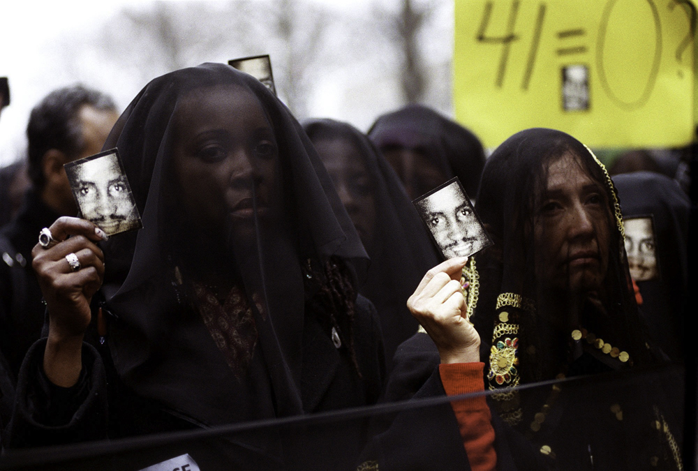 "A group called ""Women in Mourning and Outrage"" hold up photographs of Amadou Diallo during a rally in front of the United Nations. The rally was held after the acquittal of four New York City police officers involved in the shooting of Mr. Diallo, who was unarmed. February 27, 2000."