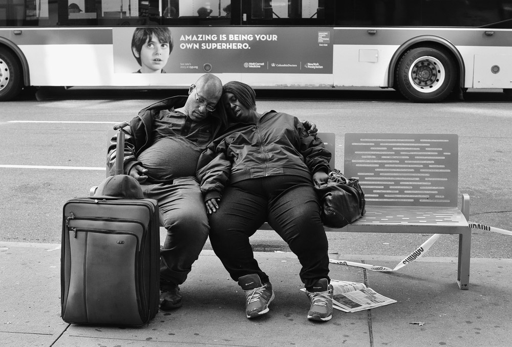 Couple sleeping together on bench on Broadway and 72nd street on Upper West Side. Sign on bus behind them reads: AMAZING IS BEING YOUR OWN SUPERHERO..EXCLUSIVE photo by Lawrence Schwartzwald